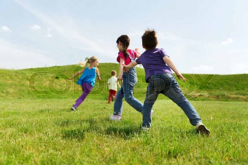 Summer, childhood, leisure and people concept - group of happy kids playing tag game and running on green field outdoors, stock photo