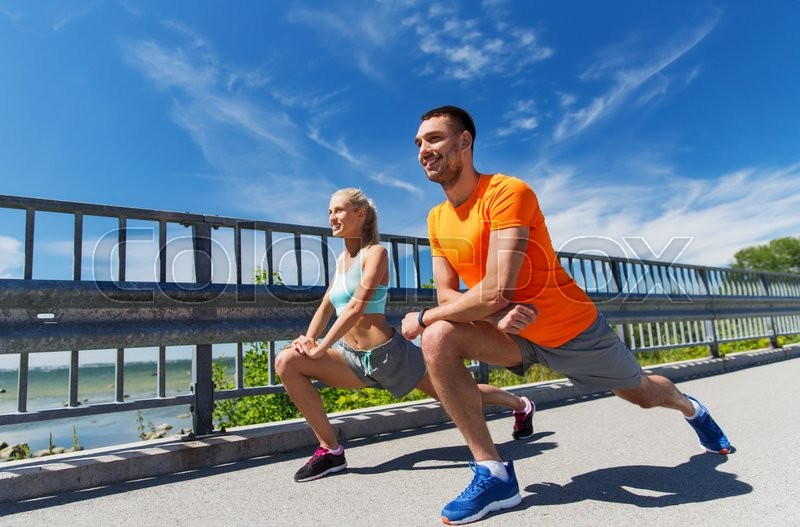 Fitness, sport, training and lifestyle concept - smiling couple stretching outdoors, stock photo