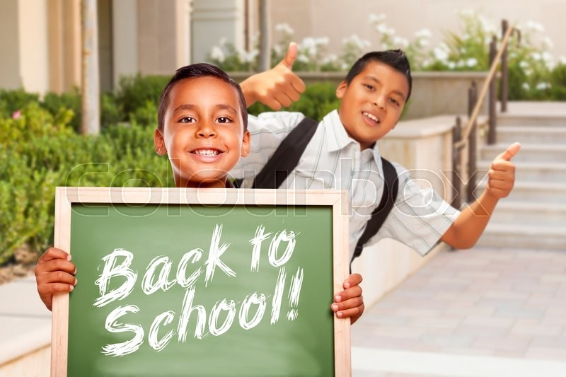 Happy Hispanic Boys Giving Thumbs Up Holding Back to School Chalk Board Outside on School Campus, stock photo