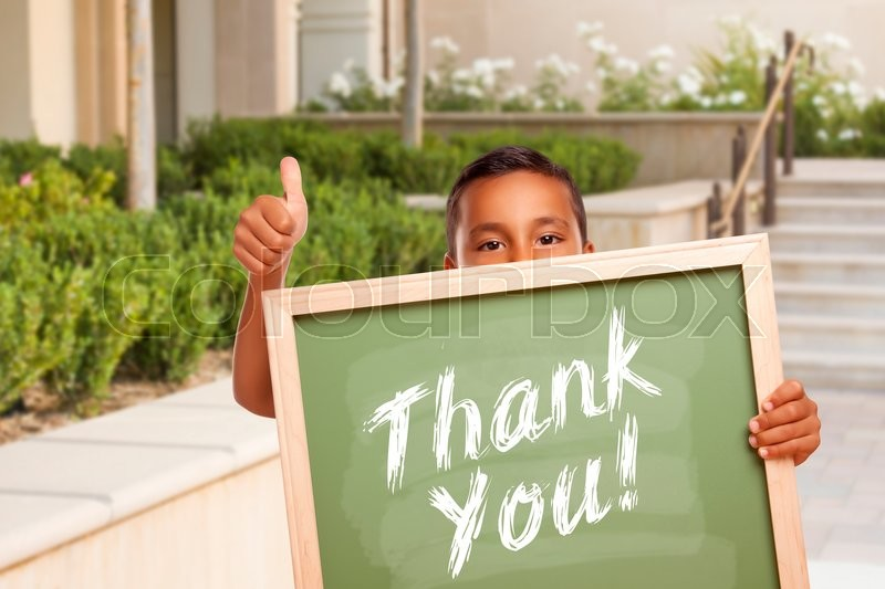 Happy Hispanic Boy Giving Thumbs Up Holding Thank You Chalk Board Outside on School Campus, stock photo