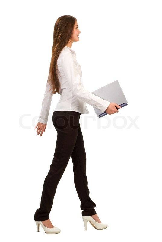 A Young Businesswoman Walking And Holding A Laptop