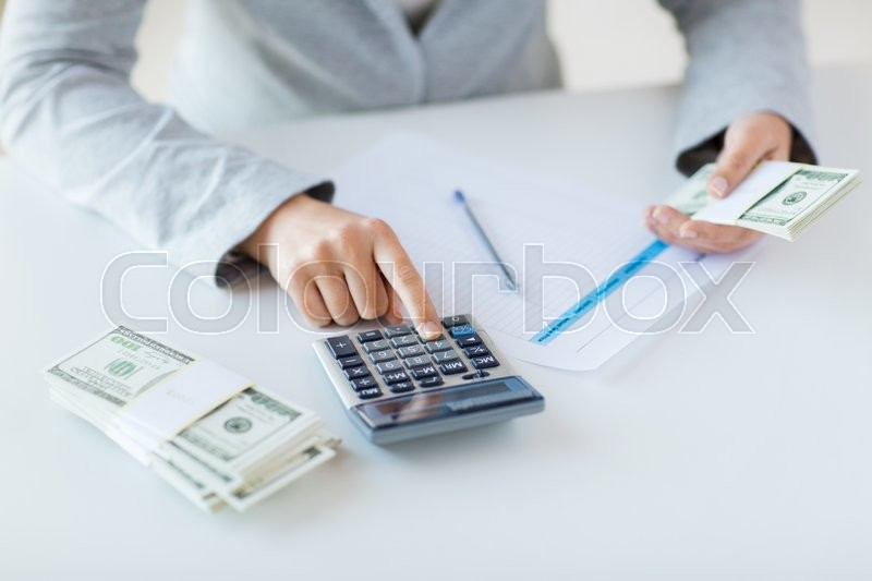 Business, finance, tax and people concept - close up of woman hands counting us dollar money with calculator, stock photo