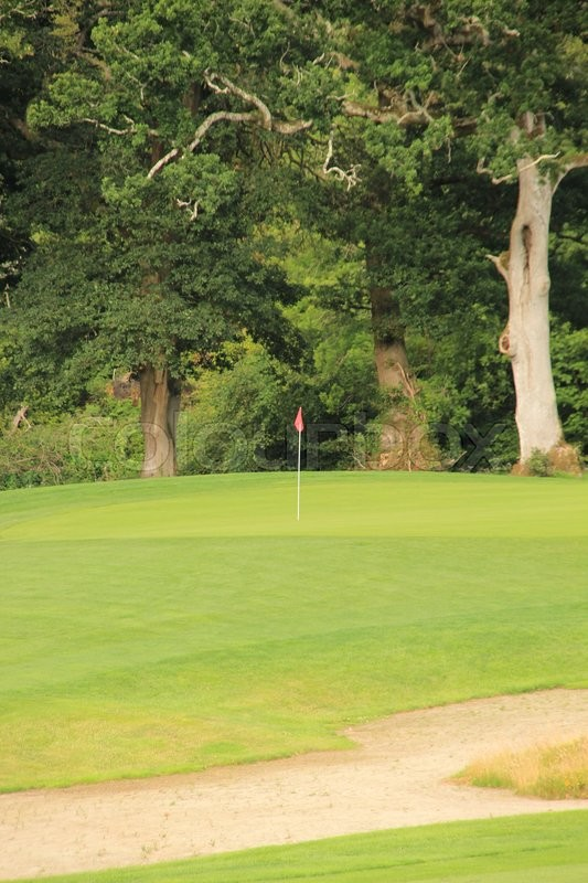 Golf field and a red flag in the hole in the summer, stock photo