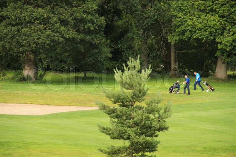 Two men with golf equipment walk over the golf court for playing a match in the summer, stock photo