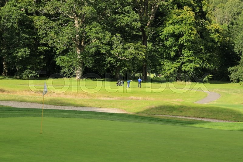 At the foreground a golf hole with a white flag and at the background two men playing a match at the golf court in the summer, stock photo