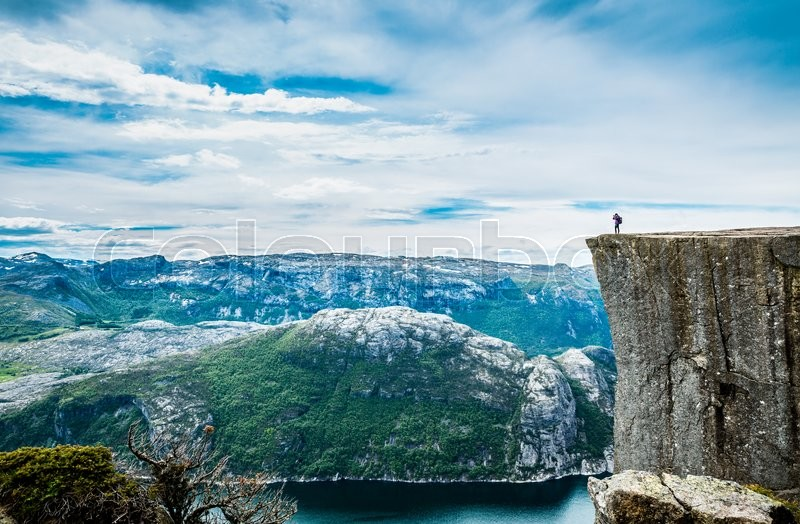 Nature photographer tourist with camera shoots while standing on top of the mountain. Beautiful Nature Norway Preikestolen or Prekestolen, stock photo