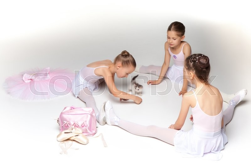 Three little ballet girls sitting in white swimsuit and pointe shoes together with cat on white background in ballet studio, stock photo