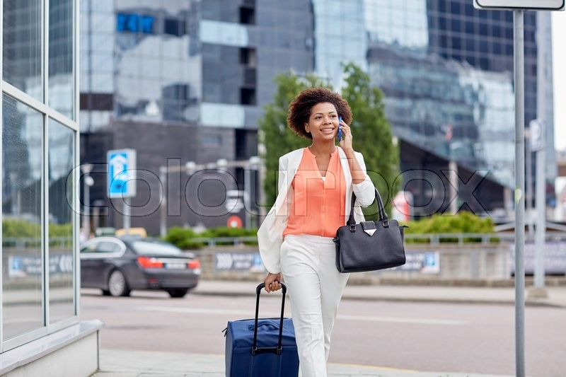 Travel, business trip, people and technology concept - happy young african american woman with travel bag walking down city street and calling on smartphone, stock photo