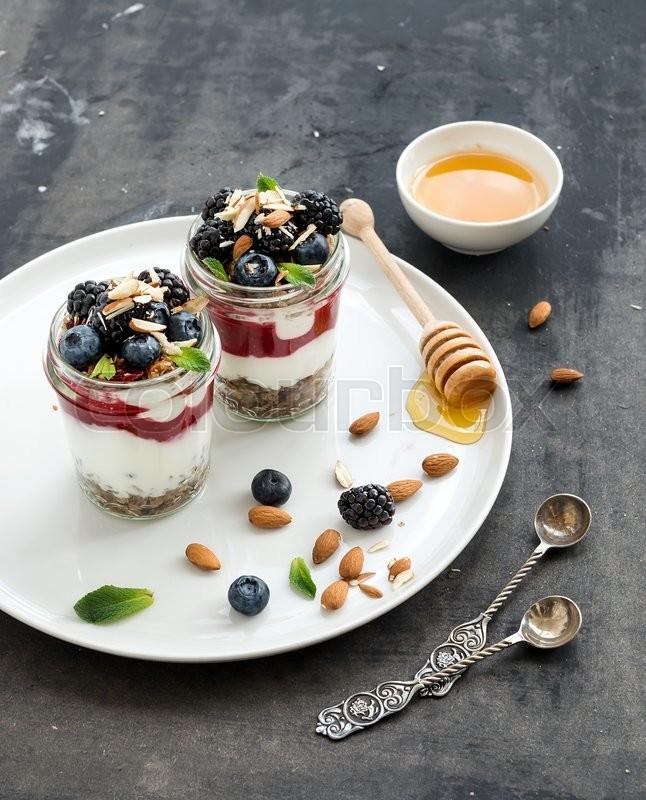 Yogurt oat granola with berries, honey and nuts in glass jars, dark grunge background, stock photo