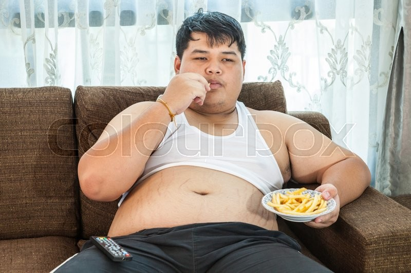 Lazy Overweight Asian Male Sitting With Stock Photo