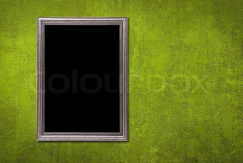 Silver frame on a green wall background, stock photo