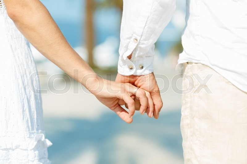 Concept shoot of friendship and love of man and woman: two hands over waterfront, stock photo