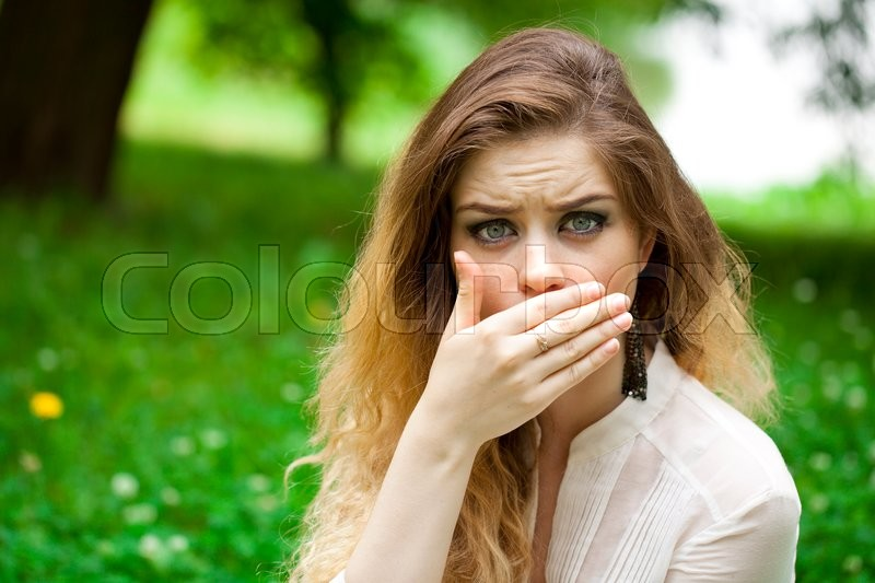 Young beautiful girl covers her mouth with his hand, posing outdoors in summer park, stock photo