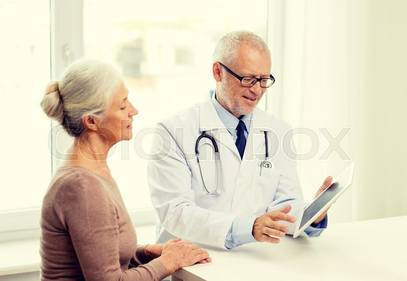 Medicine, age, health care and people concept - smiling senior woman and doctor with tablet pc computer meeting in medical office, stock photo