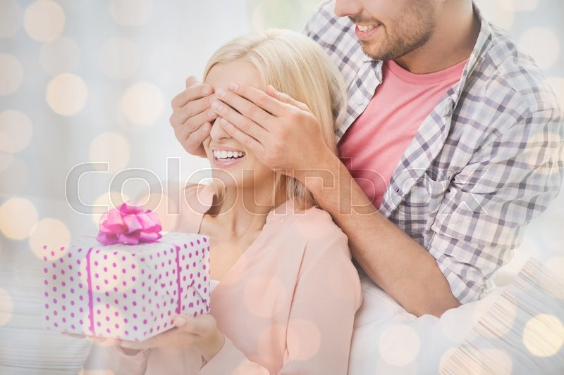 Relationships, love, people, birthday and holidays concept - happy man covering woman eyes and giving gift box over lights background, stock photo