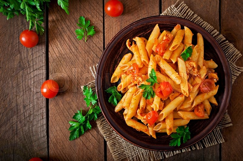 Penne pasta in tomato sauce with chicken, tomatoes decorated with parsley on a wooden table, stock photo