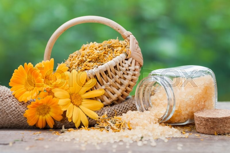 Marigold flowers, basket with dried plants and bottles of sea salt, stock photo