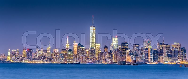 New York City Manhattan downtown skyline at dusk with skyscrapers illuminated over Hudson River panorama. Horizontal composition, copy space, stock photo
