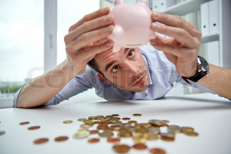 Business, people, finances, crisis and money saving concept - businessman shaking piggy bank and getting coins at office, stock photo