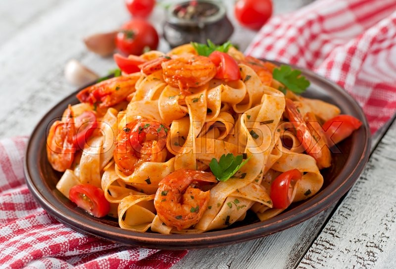 Fettuccine pasta with shrimp, tomatoes and herbs, stock photo