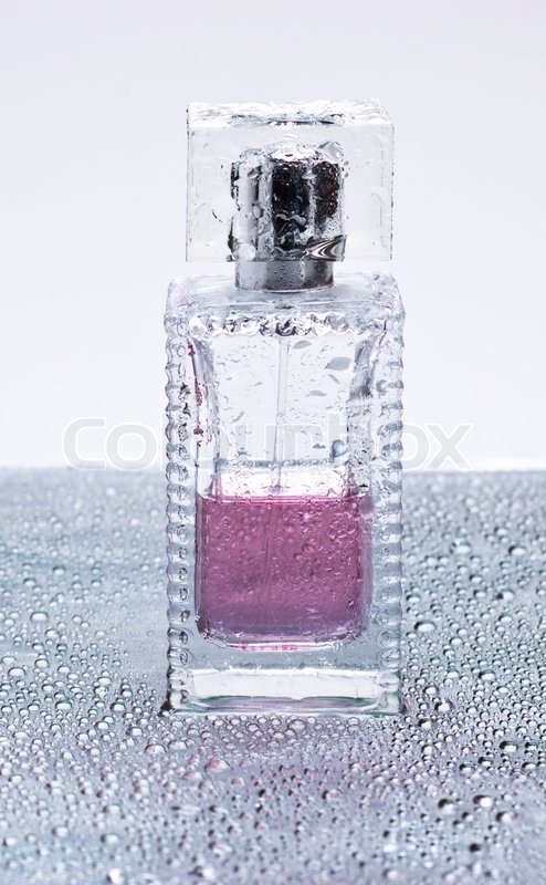 Bottle of perfume wet on the background of water drops, stock photo