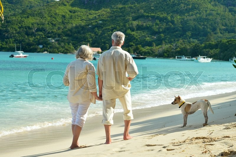 Beautiful happy elderly couple rest at tropical resort with dog, stock photo