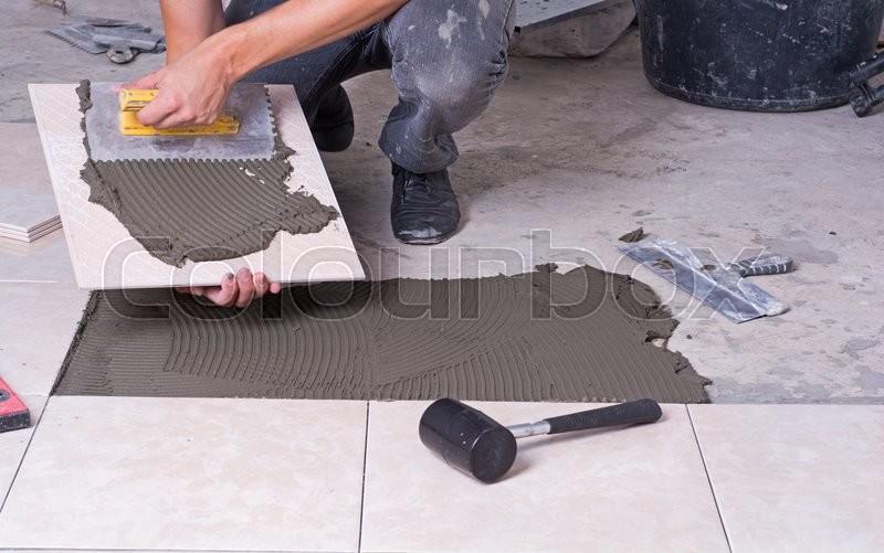 Tiler installing ceramic tiles on a floor, stock photo