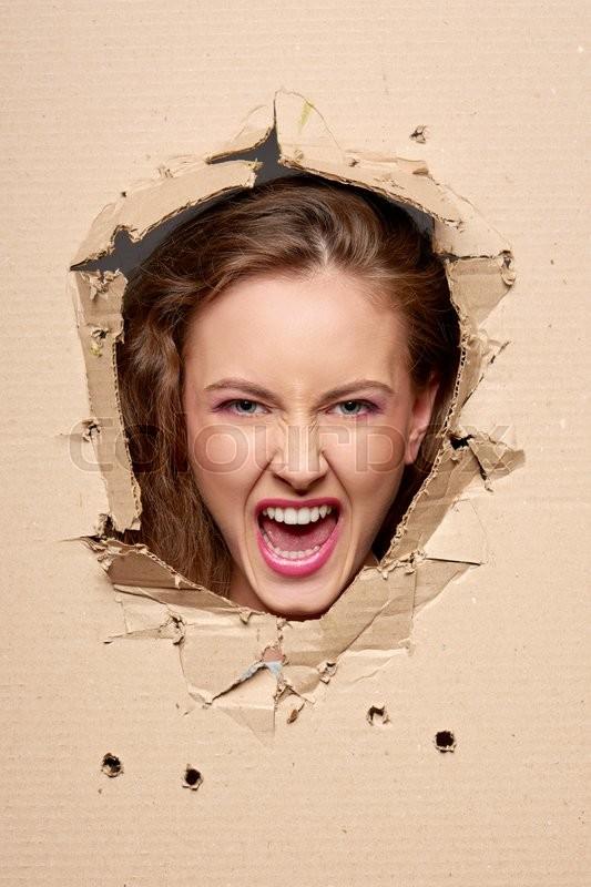 Emotional screaming girl peeping through hole in paper, stock photo
