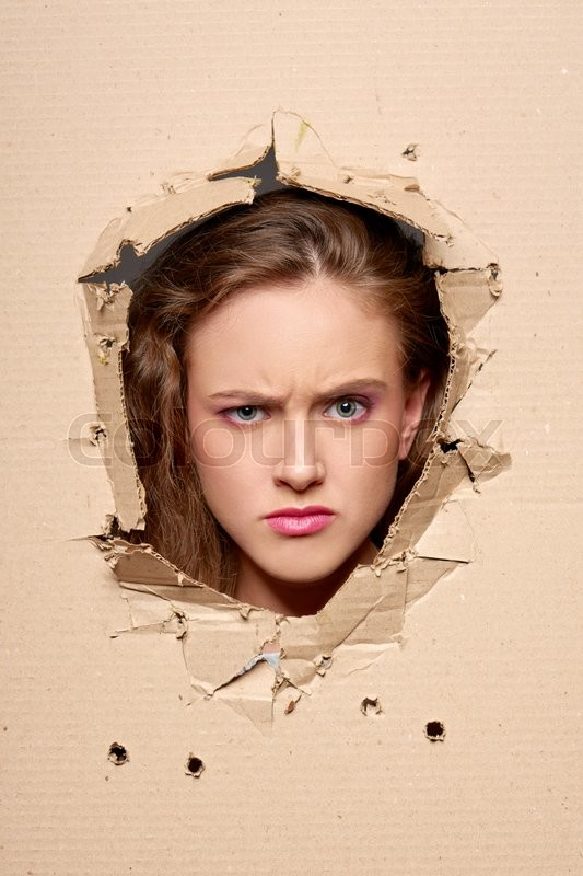 Displeased girl peeping through hole in paper, stock photo