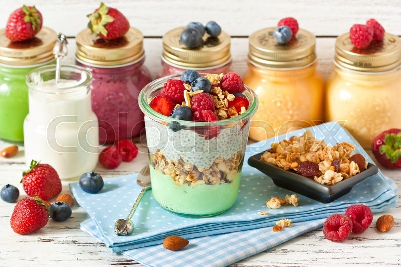 Healthy food. Fresh smoothies, glass jar of yogurt, homemade granola and breakfast with chia seeds and fresh berries, stock photo