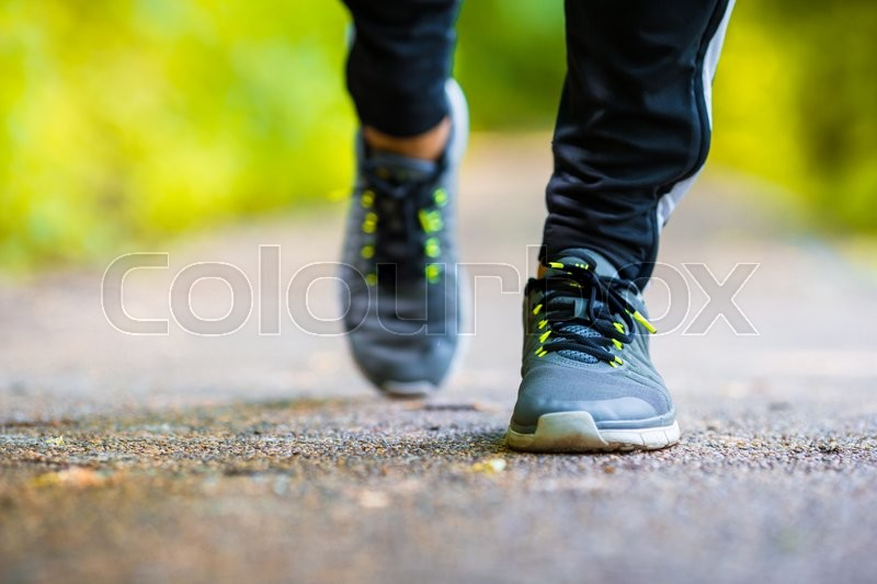 Close-up on shoe of athlete runner man feet running on road, stock photo