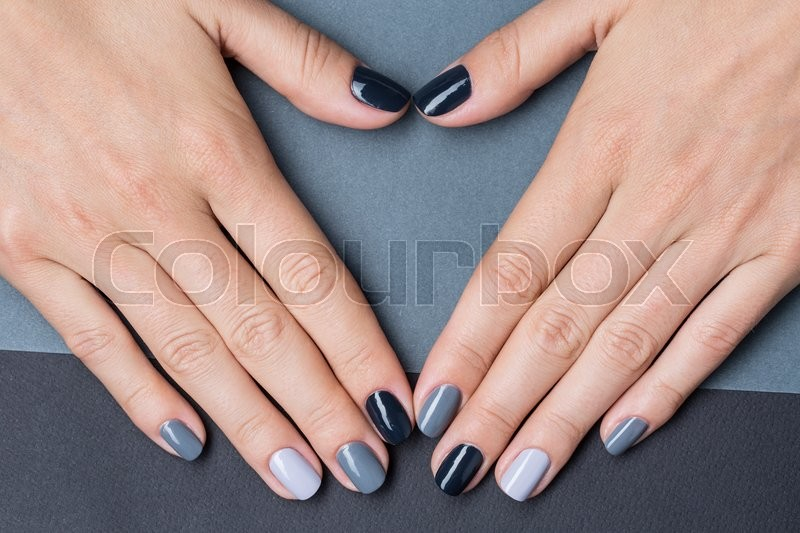 Delicate female hands with a stylish neutral manicure nail nail painted in different color gray nail polish against the backdrop of a different color gray paper background stock photo prinsesfo Image collections