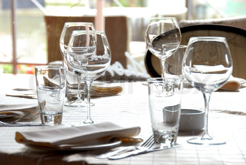 Wine Glasses And Plates Served At Dinner Table In