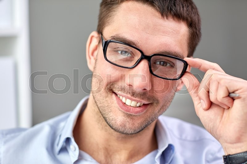 Business, people and work concept - portrait of smiling businessman in eyeglasses face in office, stock photo
