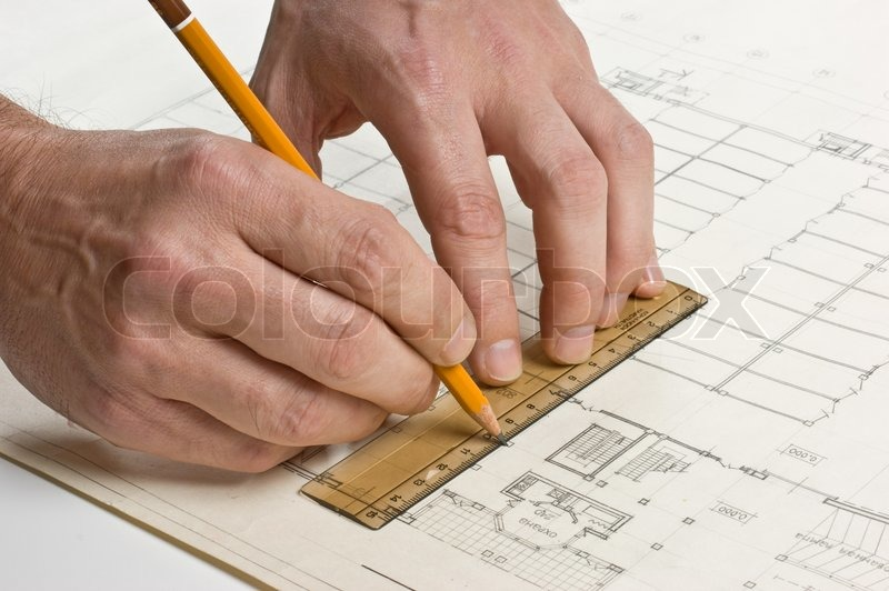 Hand draws a pencil on the drawing, stock photo
