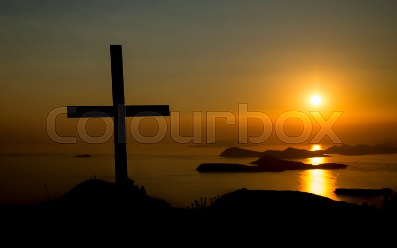 The Christianity Symbol Cross Standing At Hill During A Sunset