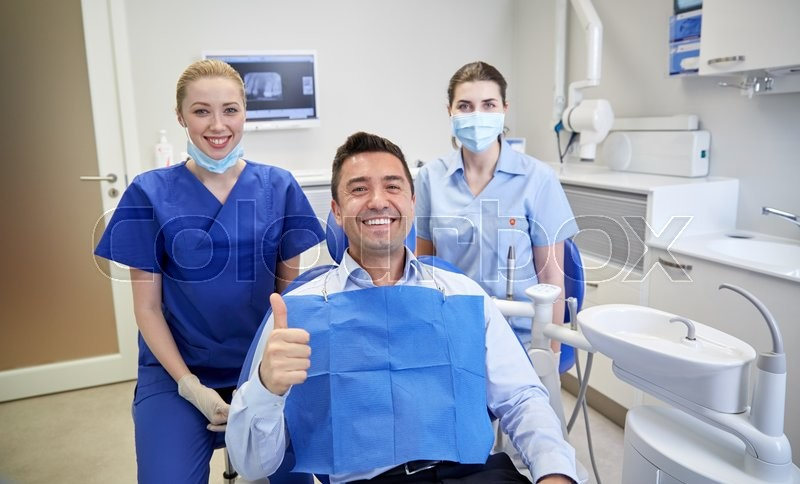 People, medicine, stomatology, gesture and health care concept - happy female dentist with assistant and man patient showing thumbs up at dental clinic office, stock photo