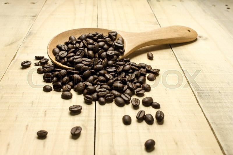 Coffee crop beans on spoon and wooden background, stock photo