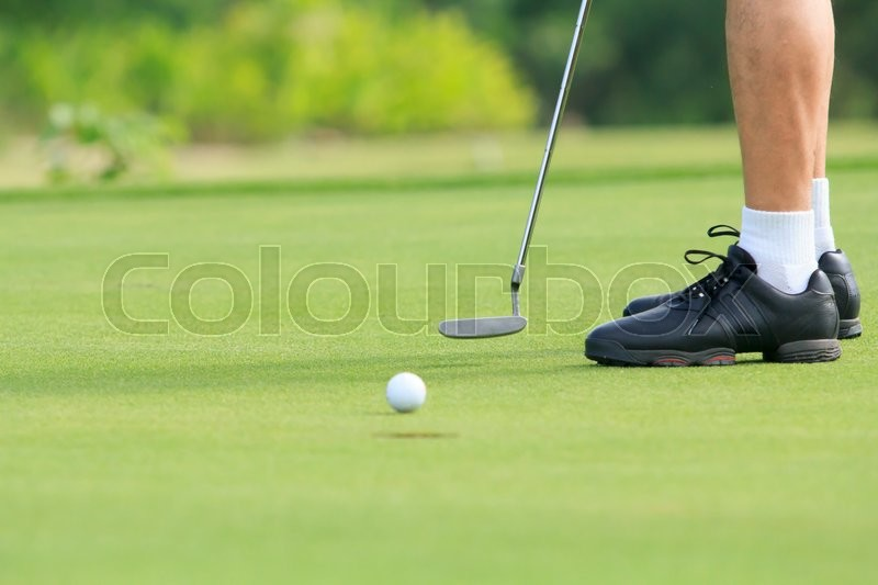 Golf man putting on green, stock photo