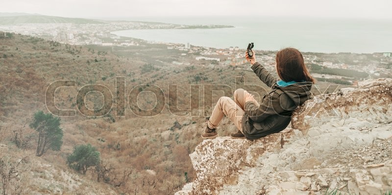 Hiker young woman sitting on peak of mountain and searching direction with a compass outdoor, stock photo