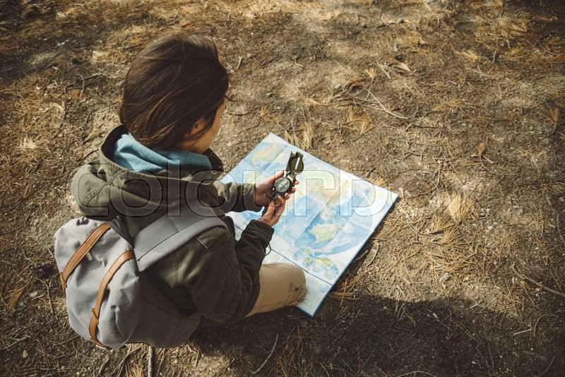 Traveler young woman with backpack searching direction with a compass on background of map in the forest. Focus on compass, stock photo