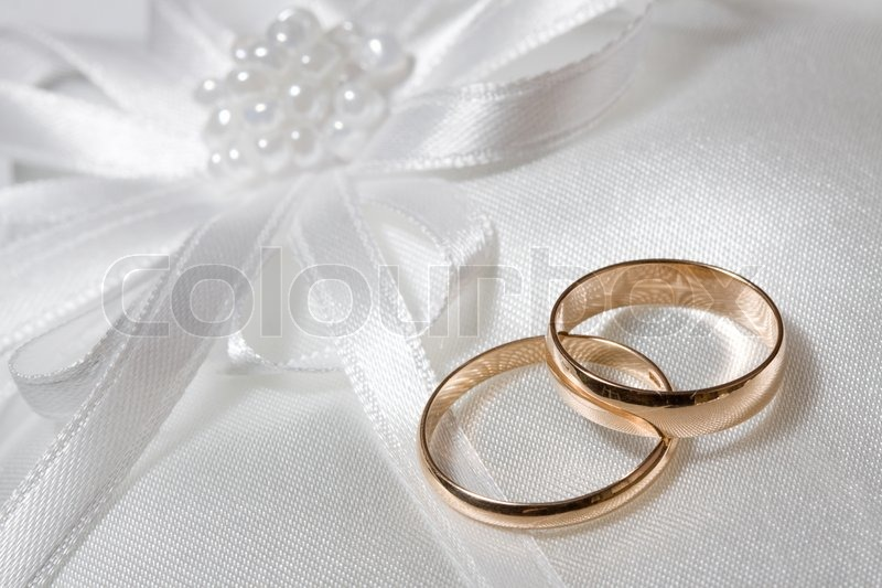 two wedding rings with white flower in stock photo