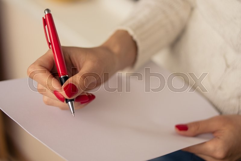 Female hands with red nails write on a sheet of paper, stock photo