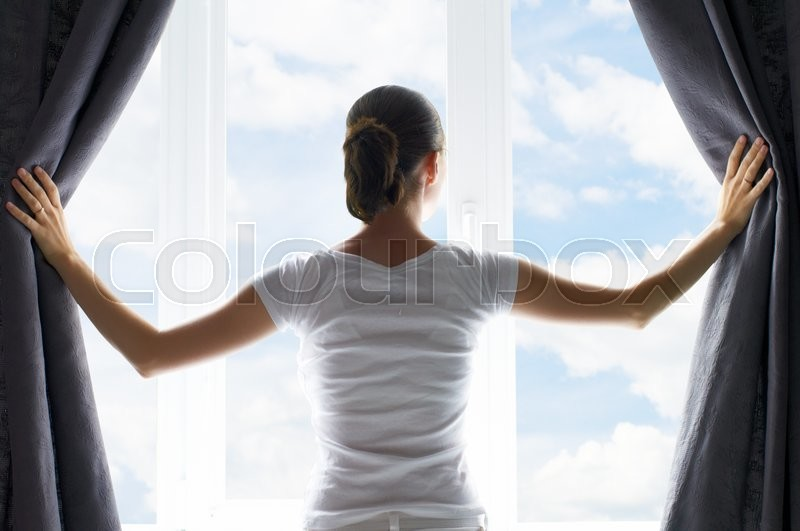 Girl opens the curtains, stock photo