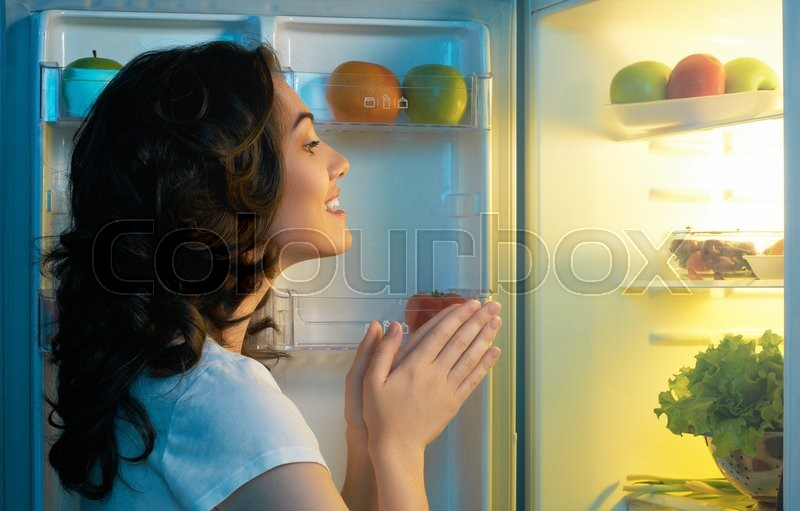 A hungry girl opens the fridge, stock photo