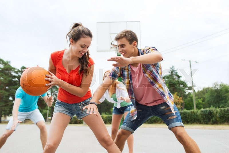 Summer vacation, sport, games and friendship concept - group of happy teenagers playing basketball outdoors, stock photo