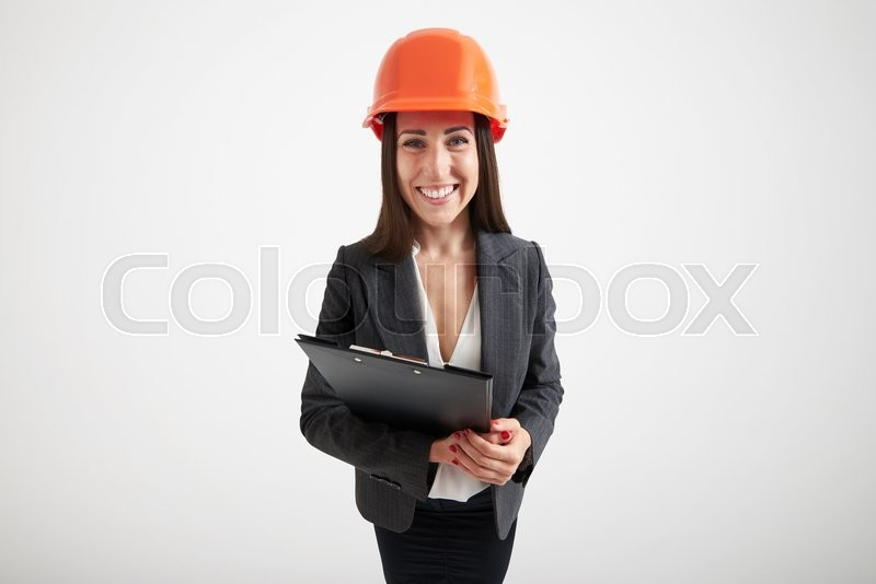 wide angle portrait of excited woman in orange hardhat holding black