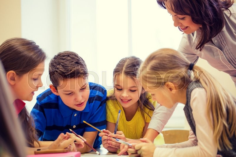 Education, elementary school, learning and people concept - teacher helping school kids writing test in classroom, stock photo