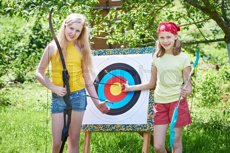 Girls with bow near sport aim in sunny summer day, stock photo