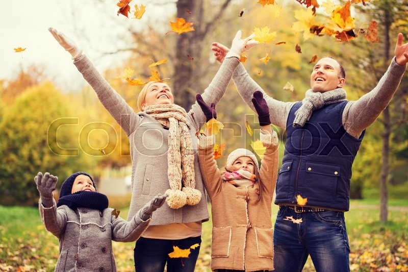 Family, childhood, season and people concept - happy family playing with autumn leaves in park, stock photo